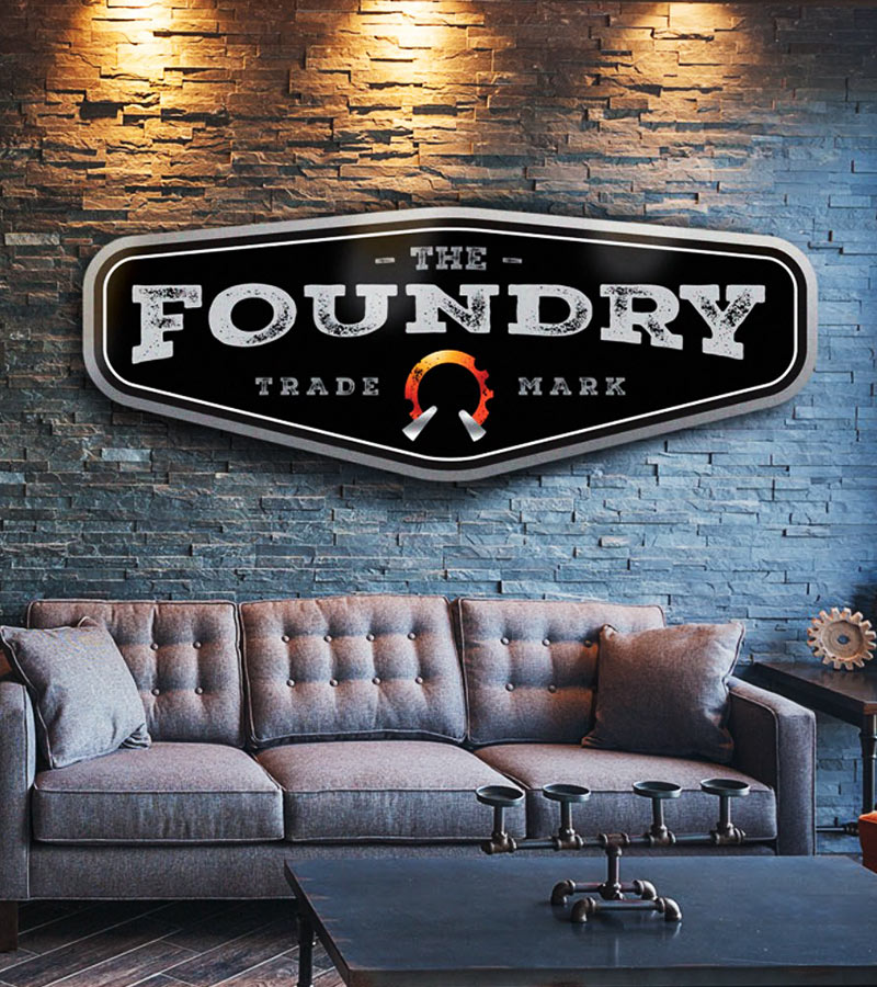 Large metal logo signage hanging in the Foundry Apartments lobby
