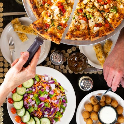 Top down shot of a table at Glass Nickel Pizza where guests are enjoying their food